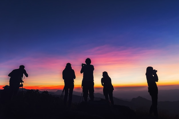 Photographers silhouettes on cliff against colorful twilight sky Premium Photo