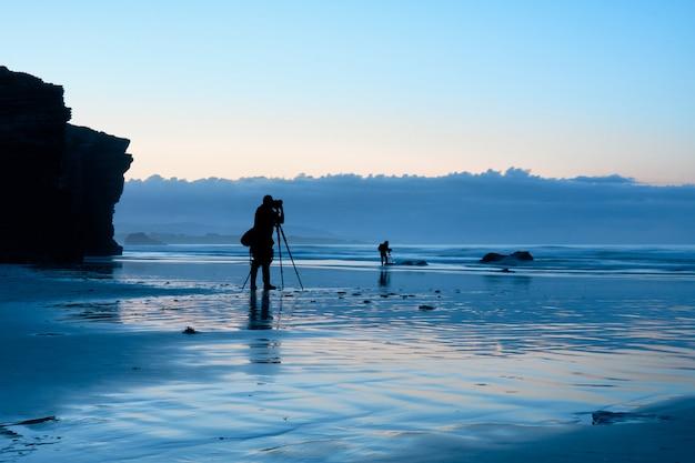 青の時間中にビーチで働く写真家 Premium写真