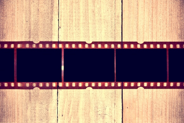 Photographic film on wooden background. Free Photo