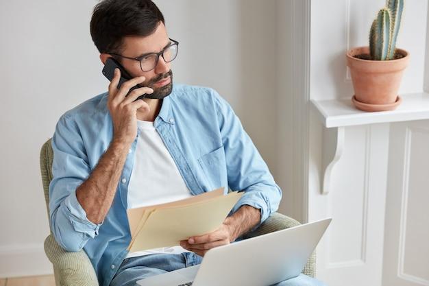 真面目な起業家の写真が彼の会社の業績について聞き、アシスタントと電話で会話する 無料写真