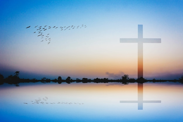 Photomontage of cross against silhoretote of mountain and lake view at sunset Premium Photo