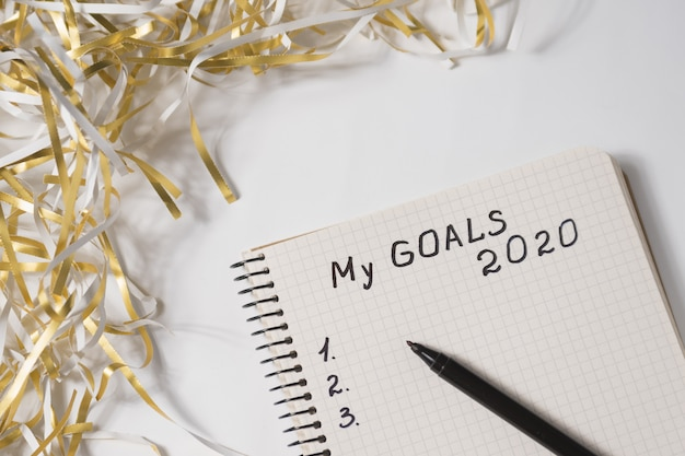 Phrase my goals 2020 in a notebook, pen, tinsel on , close up Premium Photo