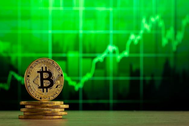 Физический биткойн, стоящий за деревянным столом перед зеленым графиком. концепция рынка bitcoin bull. Premium Фотографии
