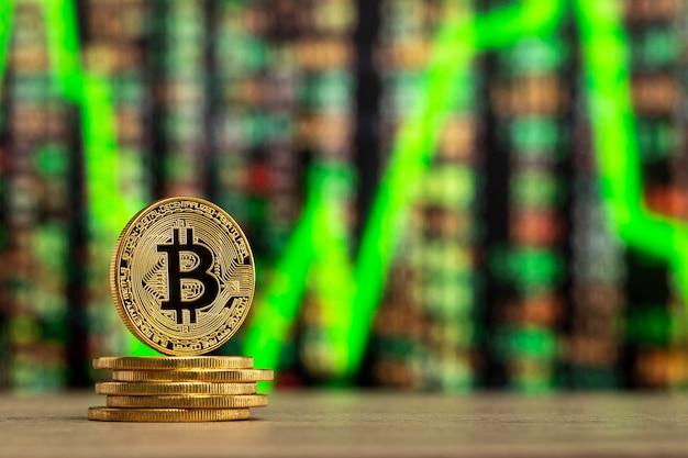 数値グラフの前の木のテーブルに立っている物理的なビットコイン Premium写真