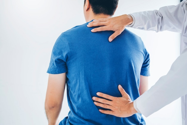 Physical doctor consulting with patient about back problems physical therapy Premium Photo