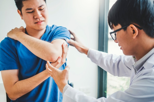 Physical doctor consulting with patient about elbow muscule pain problems physical therapy Premium Photo