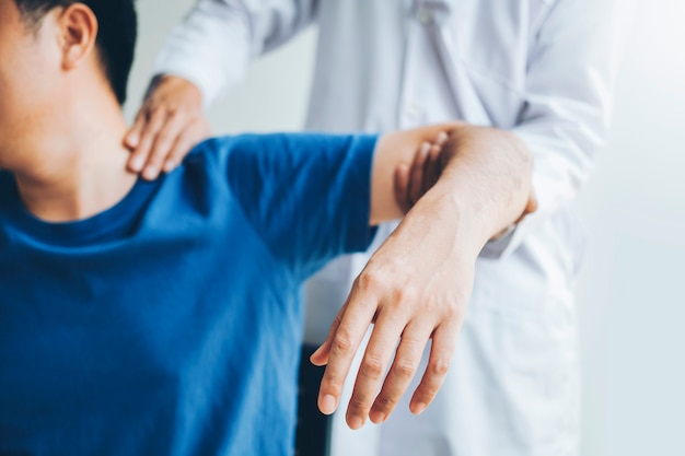 Physical doctor consulting with patient about shoulder muscule pain problems physical Premium Photo