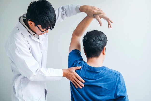 Physical doctor consulting with patient about shoulder muscule pain problems Premium Photo