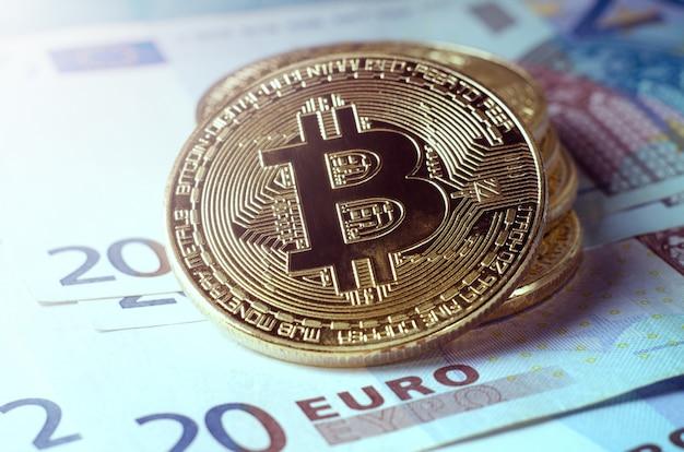 Physical gold bitcoin coin against euro bills. Premium Photo