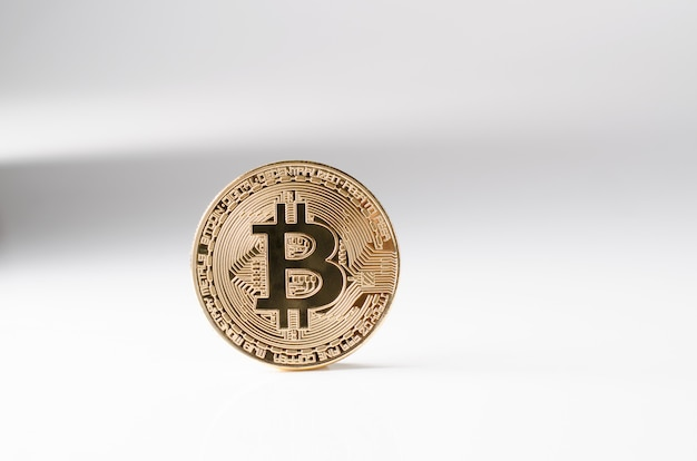 Physical gold bitcoin coin on a white background. new worldwide cryptocurrency. Premium Photo