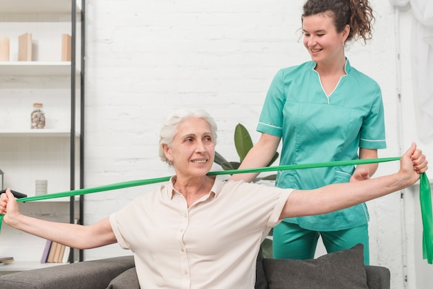 Physical therapist assisting old woman stretching with green exercise band Premium Photo