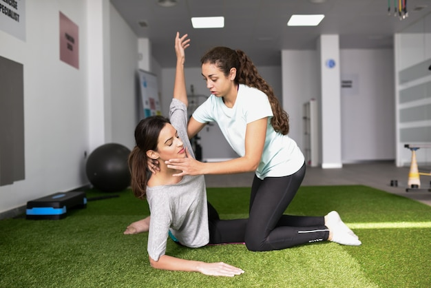 Physical therapist assisting young caucasian woman with exercise Free Photo