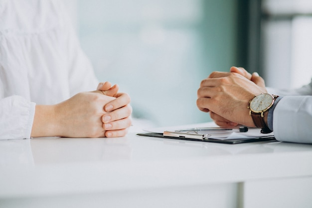 Physician consulting his patient at clinic Free Photo