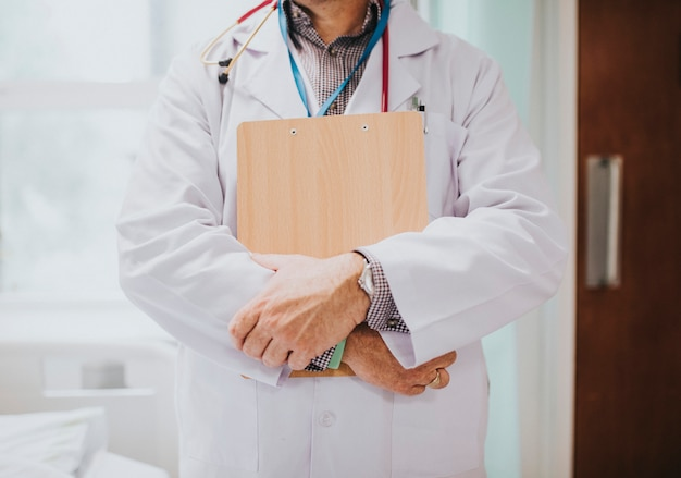 Physician holding a clipboard with medical information Free Photo
