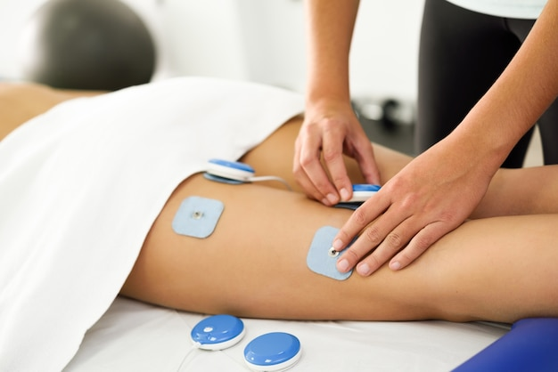 Physiotherapist applying electro stimulation in physical therapy to a young woman leg. Free Photo