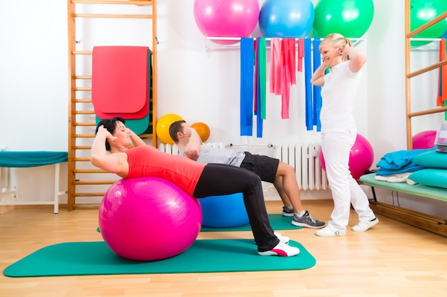 Physiotherapist giving patients gymnastic exercise Premium Photo