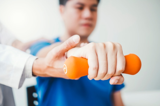 Physiotherapist man giving exercise with dumbbell treatment about arm and shoulder apy concept Premium Photo