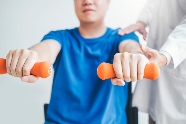 Physiotherapist man giving exercise with dumbbell treatment about arm and shoulder of athlete male patient physical therapy concept Premium Photo