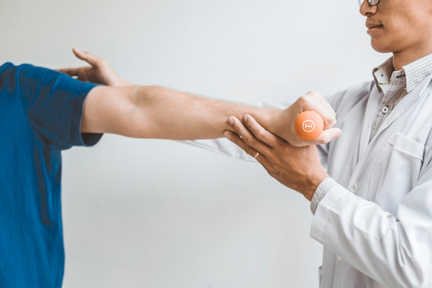 Physiotherapist man giving exercise with dumbbell treatment about arm and shoulder Premium Photo
