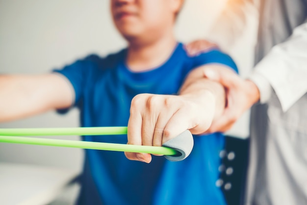 Physiotherapist man giving resistance band exercise treatment about arm and shoulder Premium Photo