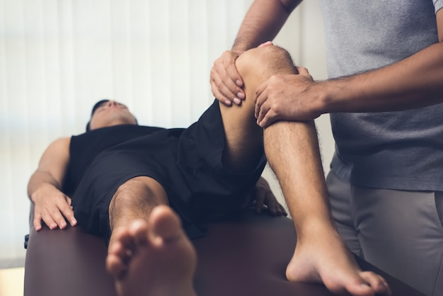 Physiotherapist treating athlete male patient Premium Photo