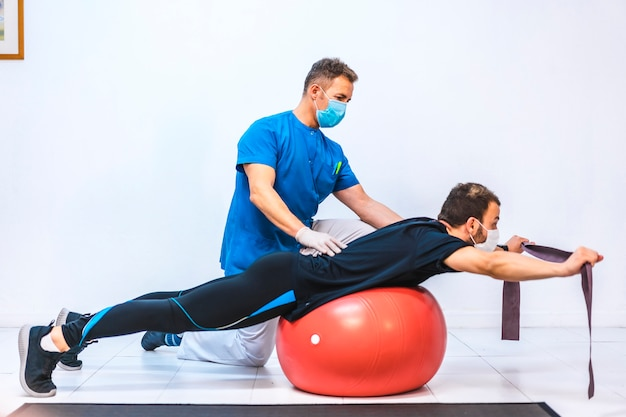 Physiotherapist with mask and a patient doing exercises with a rubber on a giant ball. physiotherapy