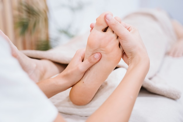 Physiotherapist woman giving a feet massage to female patient in clinic Premium Photo