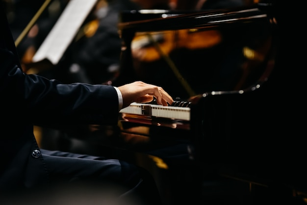Pianist playing a piece on a grand piano at a concert, seen from the side. Premium Photo