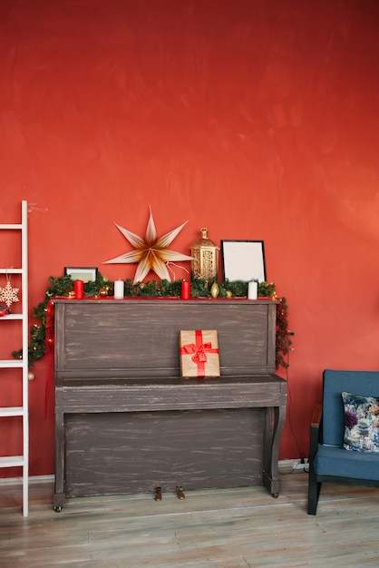 Piano and christmas decor on a red wall background Premium Photo