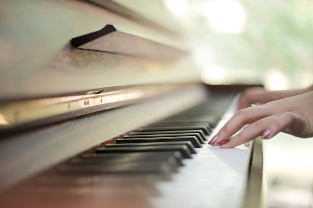 Piano keyboard with female hands playing on it Premium Photo