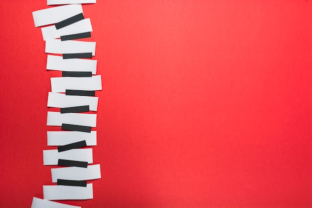 Piano keys made with black and white paper on red backdrop Free Photo