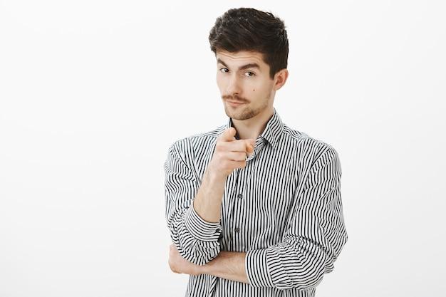 私の指導者チームで働くあなたを選ぶ。ストライプのシャツに興味をそそられる格好良いスマートな男性、人差し指で示す、好奇心旺盛な顔で額の下から見ている、提案がある 無料写真