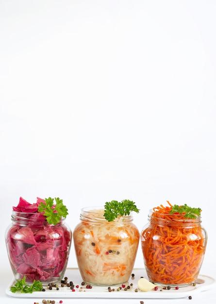 自家製野菜の漬物と発酵。ザワークラウト、赤キャベツのマリネ、ニンジン、コピースペース付きのガラスの瓶 Premium写真
