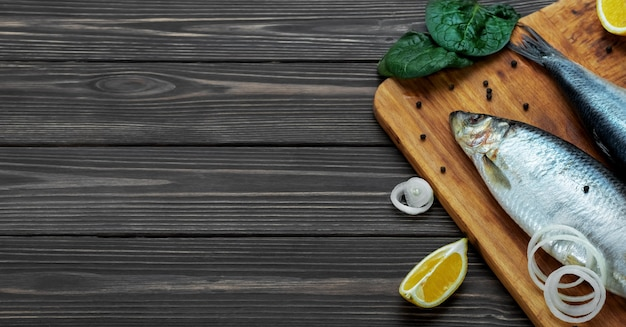 향신료와 레몬 옆 도마에 절인 대서양 청어 물고기 무료 사진