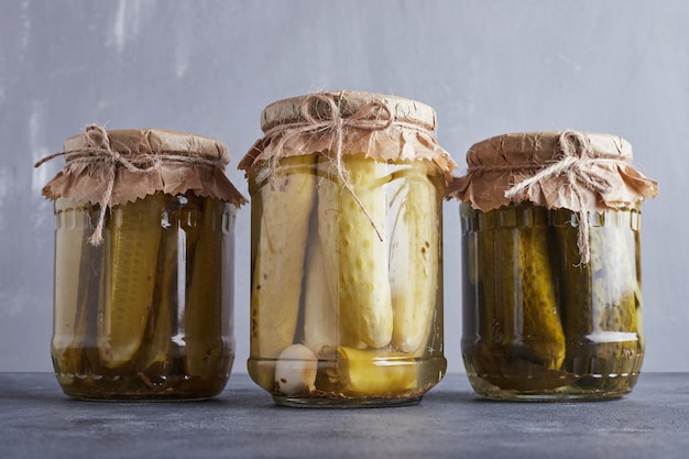 Pickled cucumbers in glass jars on blue wall. Free Photo