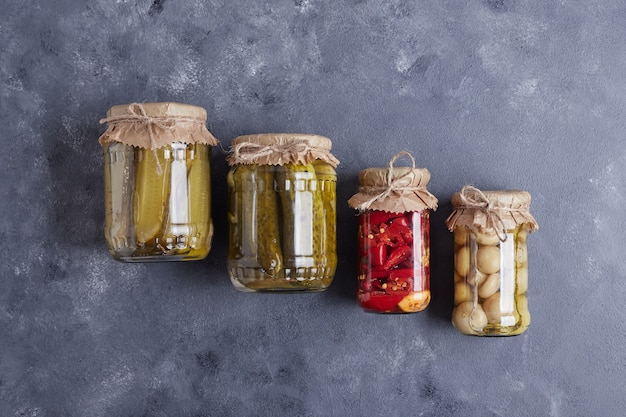 Pickled cucumbers, olives and red peppers in glass jars on blue background. Free Photo
