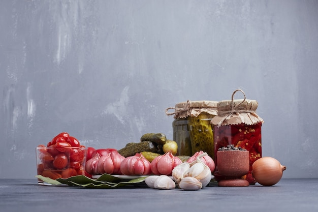 Pickled cucumbers and red peppers in glass jar with leaf, garlic, onion and grain peppers. Free Photo