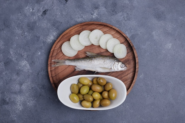 Pickled olives, fish and onion slices on wooden plate. Free Photo