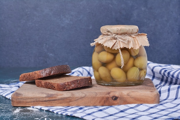 Pickled olives in glass jar with black bread slices on blue. Free Photo