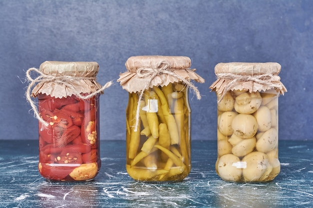 Pickled peppers and mushrooms in a glass jar on blue. Free Photo