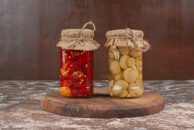Pickled red peppers and mushrooms in a glass jar on wooden plate. Free Photo