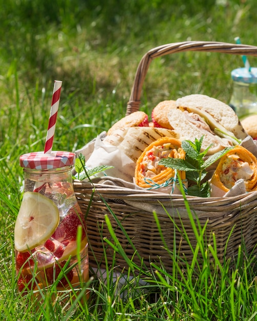 Picnic basket with food on green sunny lawn Premium Photo