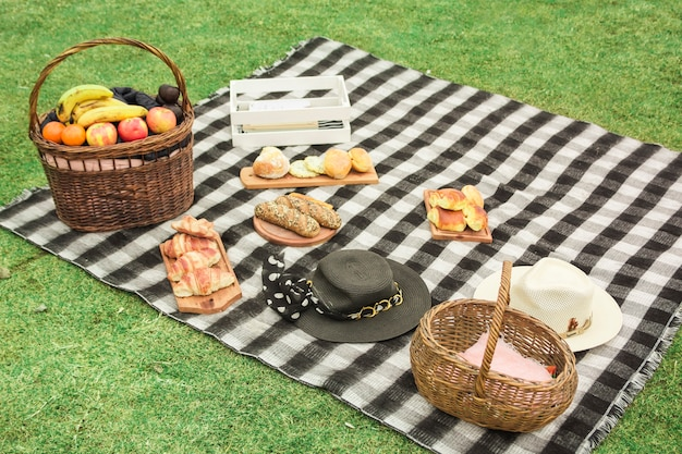 Picnic basket with fresh fruits; baked breads and hat on blanket over the green grass Free Photo