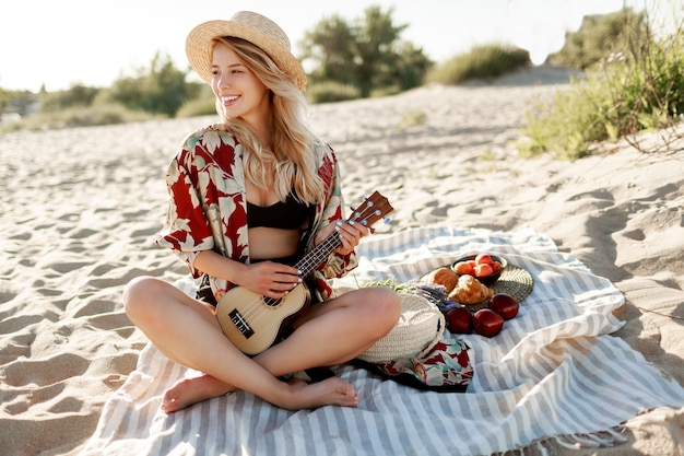 Picnic in countryside.woman in straw hat sitting on cover on the beach in sunset soft colors and playing ukulele guitar. fresh fruits, croissants and peach on the plate. Free Photo