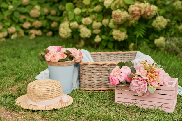 Picnic decor with pink flowers, a basket and a hat on the grass in the summer in the garden Premium Photo
