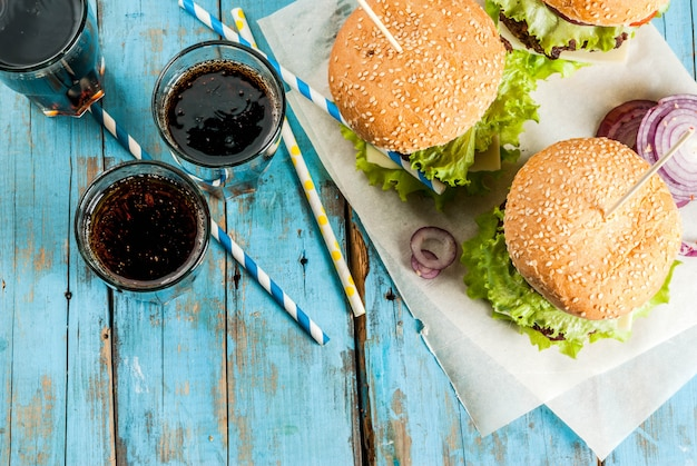 Picnic fast food unhealthy food delicious fresh tasty burgers with beef cutlet fresh vegetables and cheese on old rustic blue wooden table with sweet soda water Premium Photo