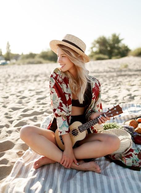 田舎でのピクニック。夕焼けの柔らかな色でビーチのカバーに座ってウクレレギターを弾く麦わら帽子のロマンチックなブロンドの女性。プレートに新鮮なフルーツ、クロワッサン、ピーチ。 無料写真