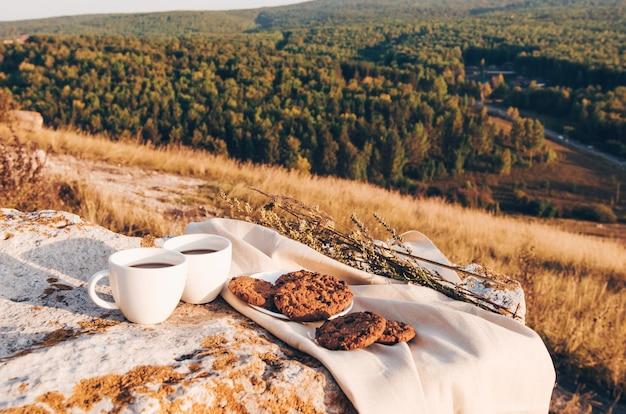 コーヒーカップと自家製クッキーを使った屋外でのピクニックランチ Premium写真