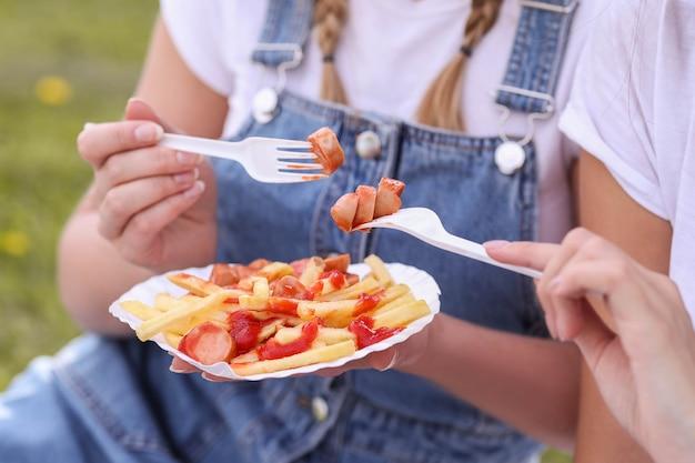 ピクニック。女性は屋外の食べ物を食べています 無料写真