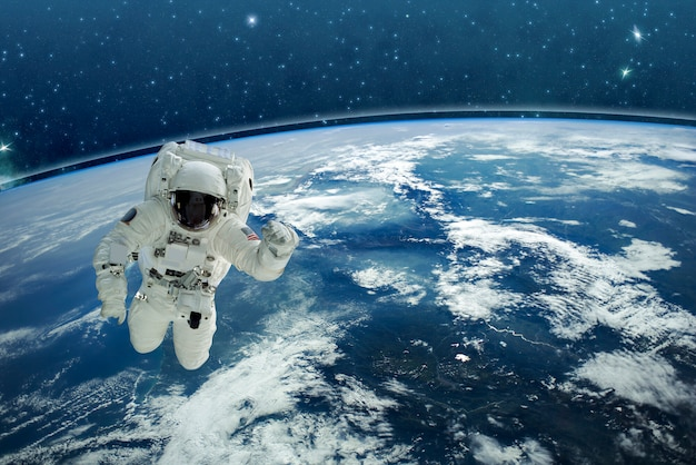 Picture of astronaut in space. in background planet earth. elements of this image furnished Premium Photo